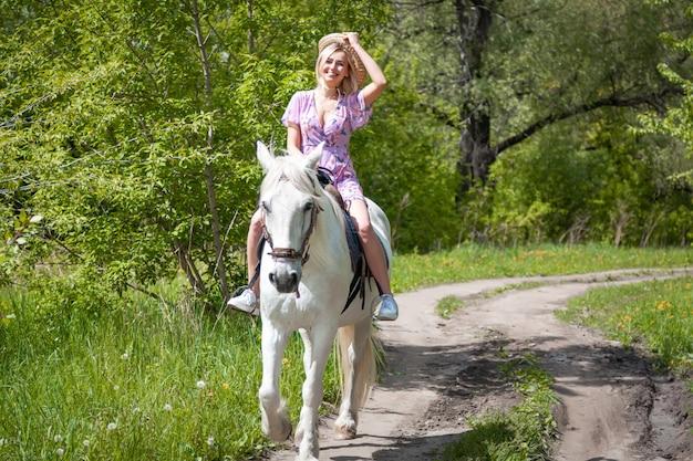 Bella giovane donna che monta cavallo bianco libero in foresta il giorno caldo di estate. fotografia all'aperto con modella e cavallo. umore di stile di vita