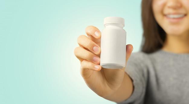 Bella giovane donna che mostra la bottiglia di pillola bianca, spazio della copia.