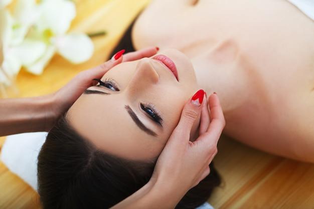 Bella giovane donna che ottiene un trattamento viso al salone di bellezza.
