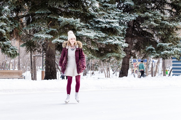 Bella giovane donna che pattina nel parco nevoso di inverno
