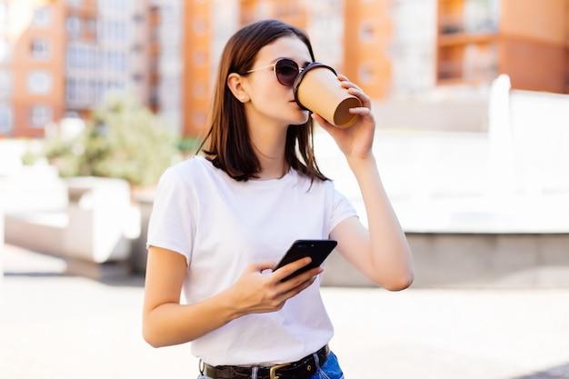 Bella giovane donna che per mezzo del suo smart phone con il sorriso mentre camminando all'aperto