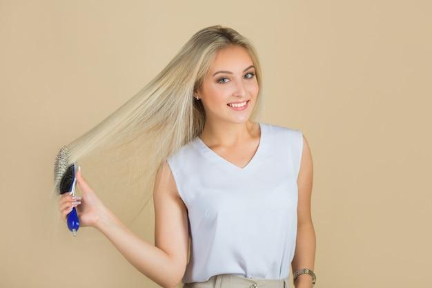 Bella giovane donna che pettina i suoi capelli
