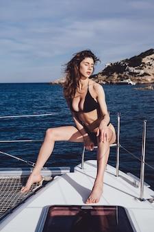 Bella giovane donna che posa su uno yacht
