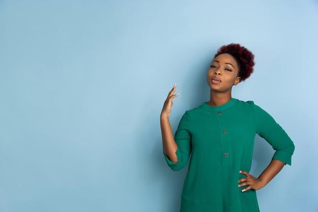 Bella giovane donna che posa sulla parete blu
