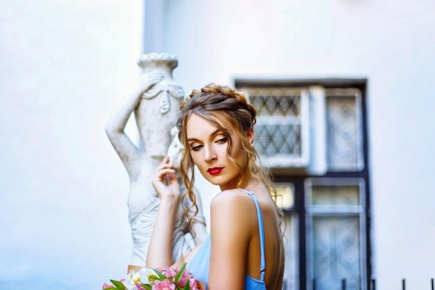 Bella giovane donna che posa vicino ad una statua greca