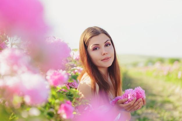 Bella giovane donna che posa vicino alle rose in un giardino,