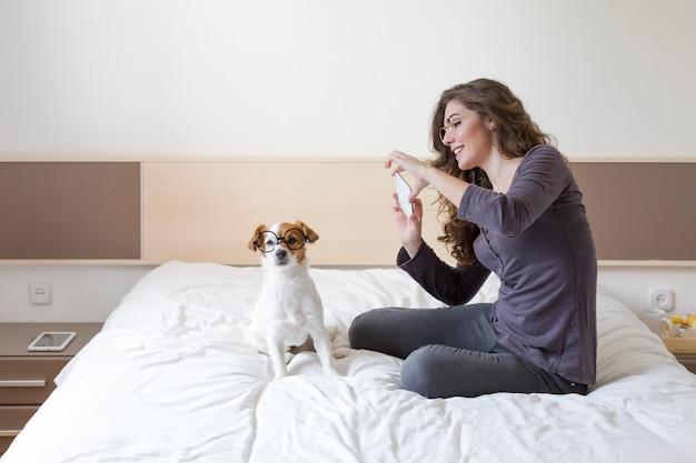 Bella giovane donna che prende un selfie con il telefono cellulare sul letto con il suo piccolo cane sveglio inoltre. casa, interni e stile di vita