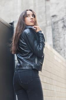 Bella giovane donna che regola la sua giacca collo in pelle