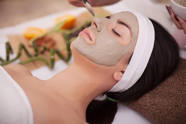Bella giovane donna che riceve maschera facciale grigia nel salone di bellezza