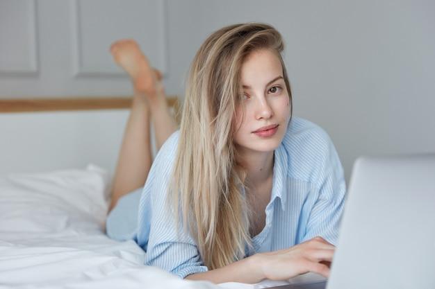 Bella giovane donna che si distende a letto con il computer portatile