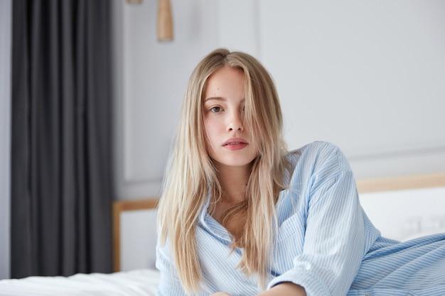 Bella giovane donna che si distende a letto