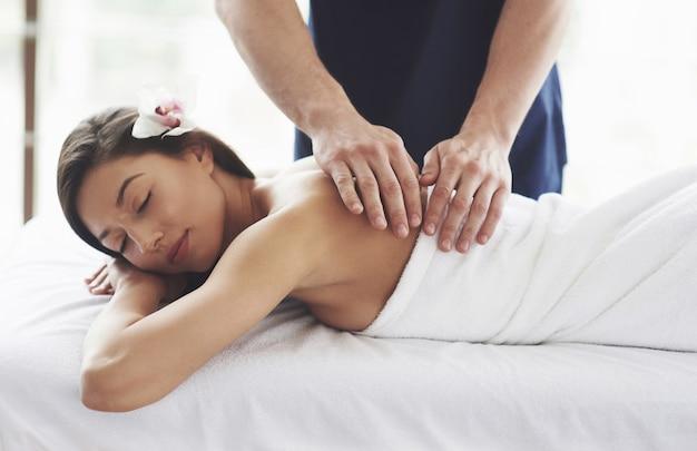 Bella giovane donna che si distende con il massaggio della mano alla stazione termale di bellezza.