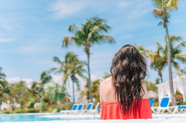 Bella giovane donna che si distende nella piscina.