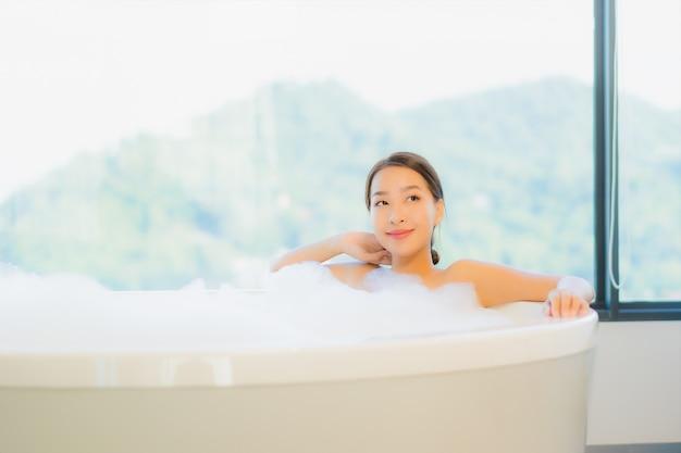 Bella giovane donna che si distende nella vasca da bagno