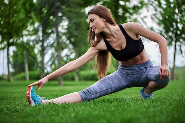 Bella giovane donna che si esercita all'aperto allungando una delle sue gambe