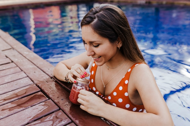Bella giovane donna che si rilassa allo stagno. tenendo un succo sano e rilassante estate e stile di vita