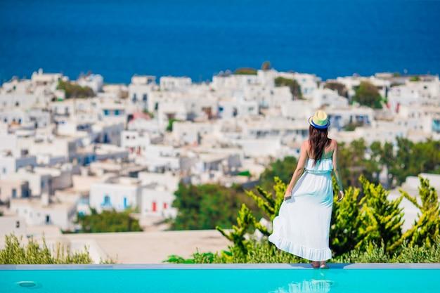 Bella giovane donna che si rilassa vicino allo stagno con la vista stupefacente su mykonos, grecia