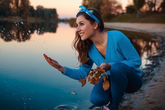 Bella giovane donna che si siede alla sponda del fiume di autunno che spruzza acqua