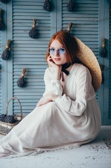Bella giovane donna che si siede con la lavanda contro la parete blu.