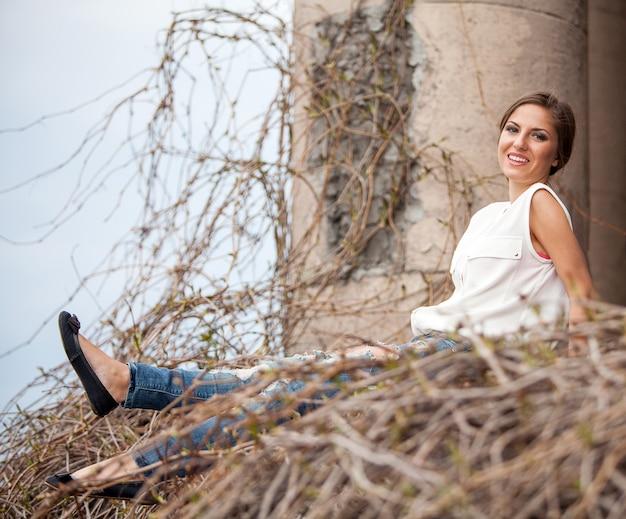 Bella giovane donna che si siede in una vite