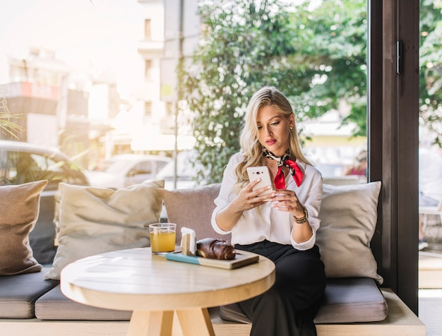 Bella giovane donna che si siede nel caf� facendo uso del telefono cellulare