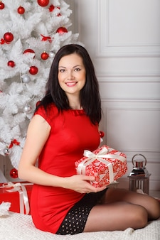 Bella giovane donna che si siede sul pavimento vicino all'albero di natale con i regali