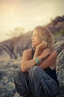 Bella giovane donna che si siede sulle rocce al tramonto