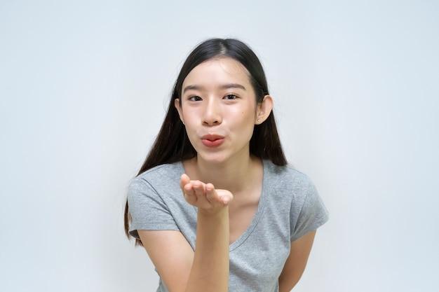 Bella giovane donna che soffia bacio, ritratto, ragazza asiatica