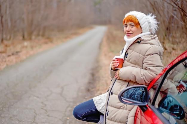 Bella giovane donna che sorride, bevendo caffè da una tazza di carta accanto alla macchina rossa sullo sfondo della foresta di autunno