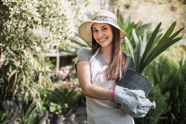 Bella giovane donna che sta nella pianta da vaso della tenuta del giardino