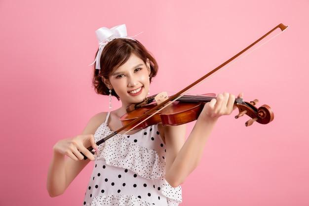 Bella giovane donna che suona il violino sopra il rosa