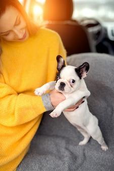Bella giovane donna che tiene adorabile cagnolino tra le braccia.