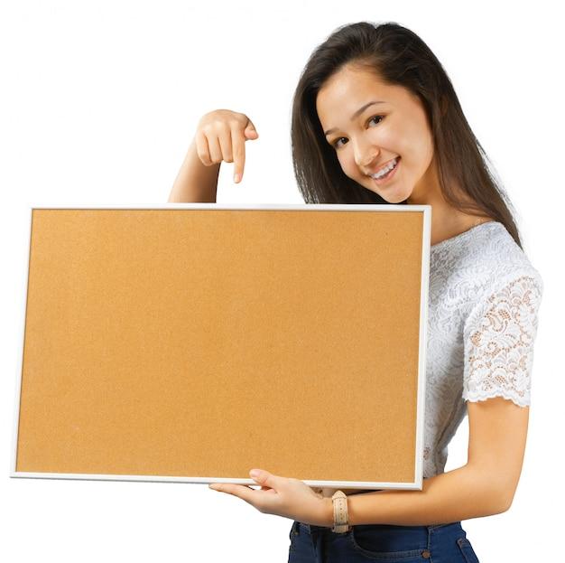 Bella giovane donna che tiene carta in bianco, isolata su bianco