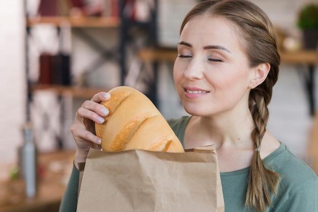 Bella giovane donna che tiene pane fresco