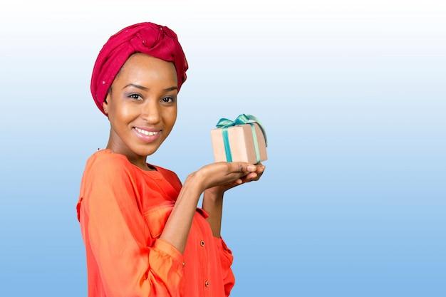Bella giovane donna che tiene un regalo
