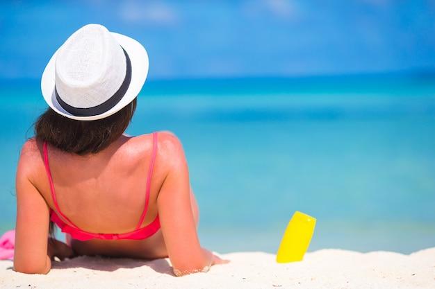 Bella giovane donna che tiene un suncream sdraiato sulla spiaggia tropicale