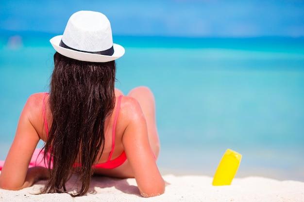 Bella giovane donna che tiene una crema solare che si trova sulla spiaggia tropicale