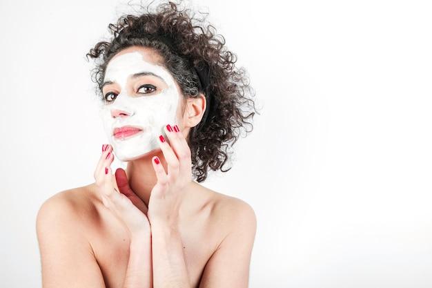 Bella giovane donna che tocca la sua maschera di protezione isolato su priorità bassa bianca