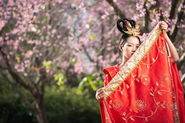 Bella giovane donna cinese che indossa cheongsam tradizionale rosso in giardino di fiori di ciliegio