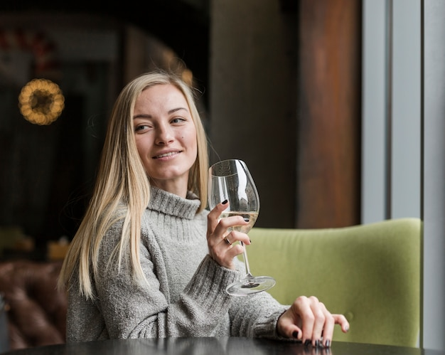 Bella giovane donna con bicchiere di vino che osserva via