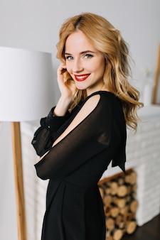 Bella giovane donna con capelli biondi ondulati in camera con mobili bianchi, godendo una buona giornata a casa. indossa un abito nero elegante, trucco da giorno leggero con rossetto rosso.