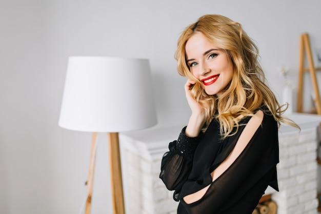 Bella giovane donna con capelli ondulati biondi in posa in camera accogliente con mobili bianchi, godendo una buona giornata a casa. indossa un'elegante camicetta nera, trucco da giorno leggero con rossetto rosso.