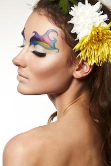 Bella giovane donna con delicati fiori tra i capelli