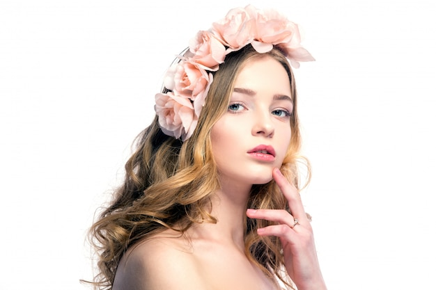 Bella giovane donna con fiori rosa sulla testa