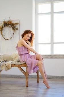 Bella giovane donna con i capelli rossi, seduto in studio.