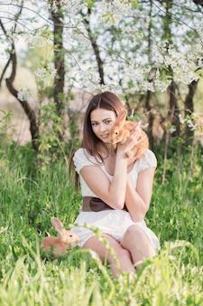 Bella giovane donna con i conigli in giardino
