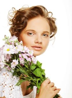 Bella giovane donna con i fiori del mazzo