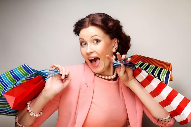 Bella giovane donna con i sacchetti della spesa colorati