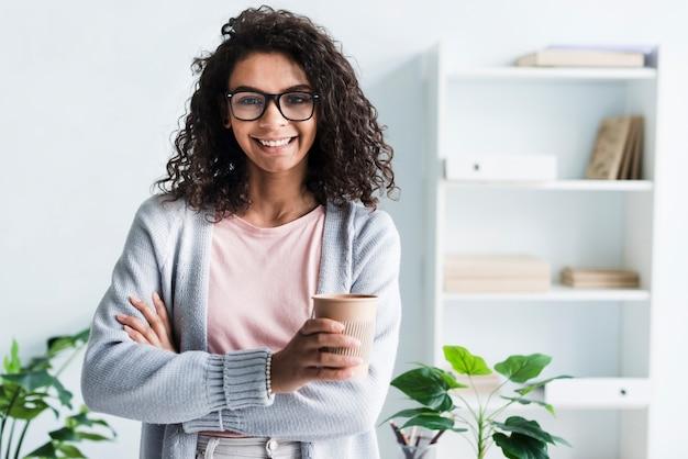 Bella giovane donna con la tazza di carta in ufficio