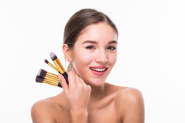 Bella giovane donna con le spazzole di trucco vicino al suo fronte isolato sulla parete bianca